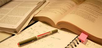 open books with notebook and pen on top of it representing research